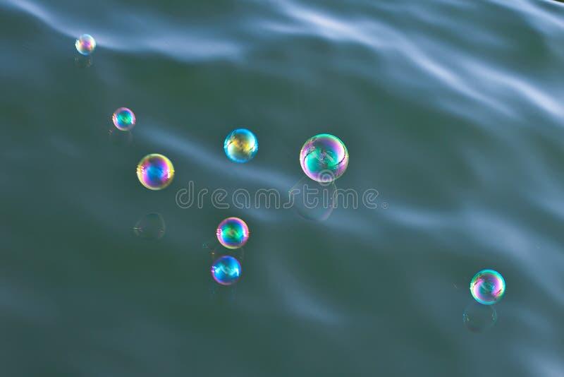 Sabão-bolhas brilhantes sobre a água foto de stock royalty free