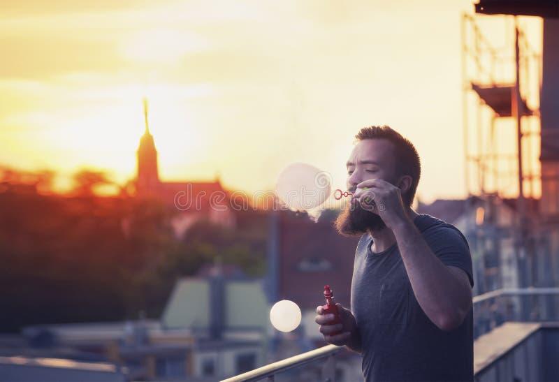 Sabão de sopro das bolhas do homem farpado considerável novo do moderno no terraço No fundo, nivelando o por do sol sobre a cidad fotos de stock