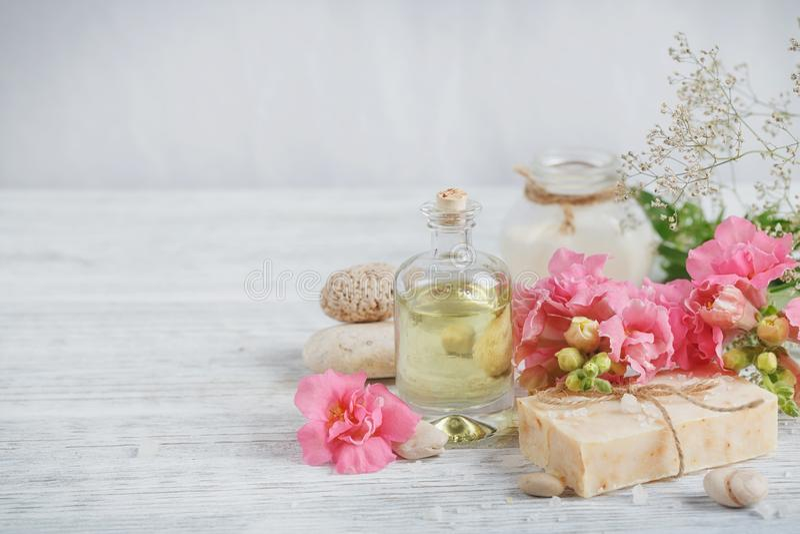 Sabão feito a mão natural, óleo aromático e flores em de madeira branco imagem de stock royalty free