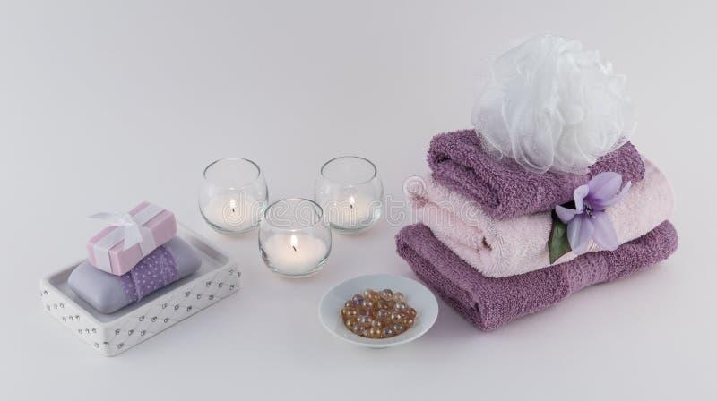 Sabão, grânulos do óleo de banho, e toalhas luxuosos com velas fotos de stock royalty free