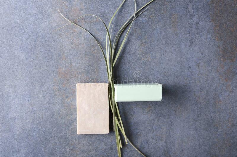 Sab?es de barra e planta secada na superf?cie escura, vista superior Conceito do sabão orgânico com ervas imagem de stock royalty free