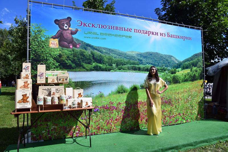 Sabantui celebration in Moscow. A woman poses for photos by honey stand royalty free stock photos