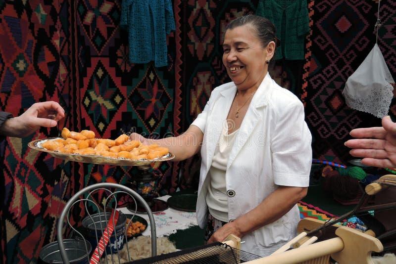 Sabantui-Feier in Moskau Frau bietet traditionelle Bonbons an, um zu schmecken stockbilder
