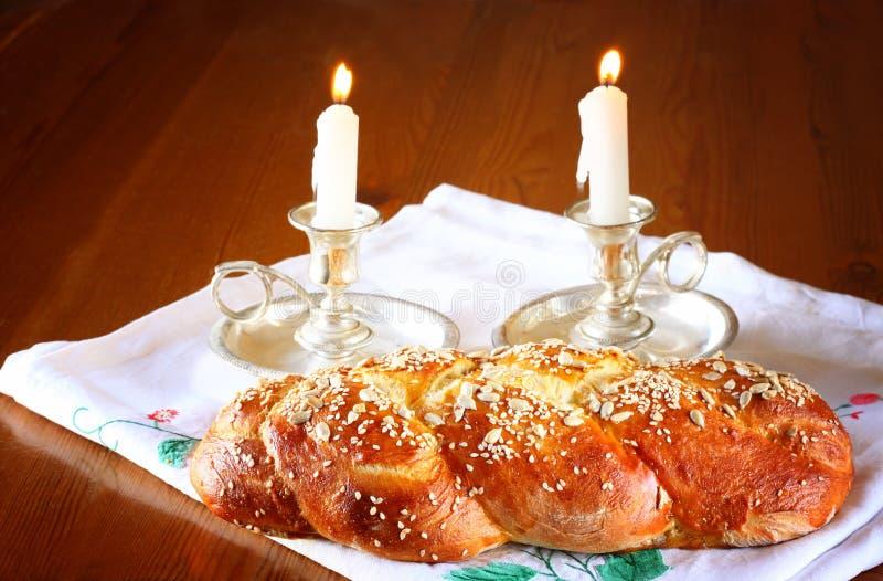 Sabbatbeeld. challah brood en candela's op houten lijst stock foto