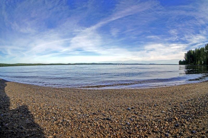 Sabbia bagnata sulla riva del lago di mattina con un cielo blu e le nuvole pennute leggere fotografie stock libere da diritti