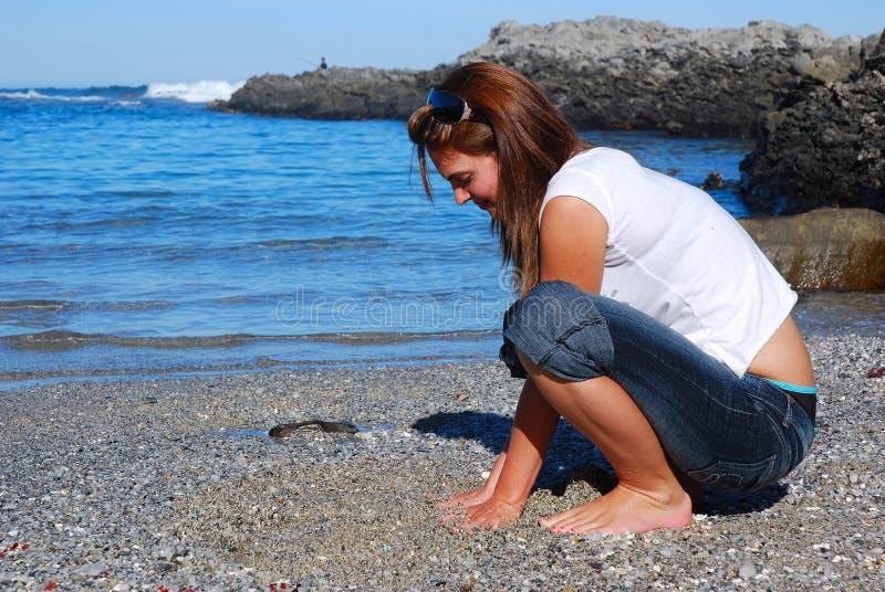 Sabbia commovente della spiaggia della donna fotografia stock