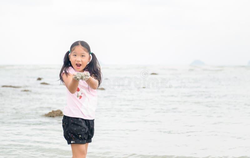 Sabbia del gioco della bambina sulla spiaggia immagini stock libere da diritti