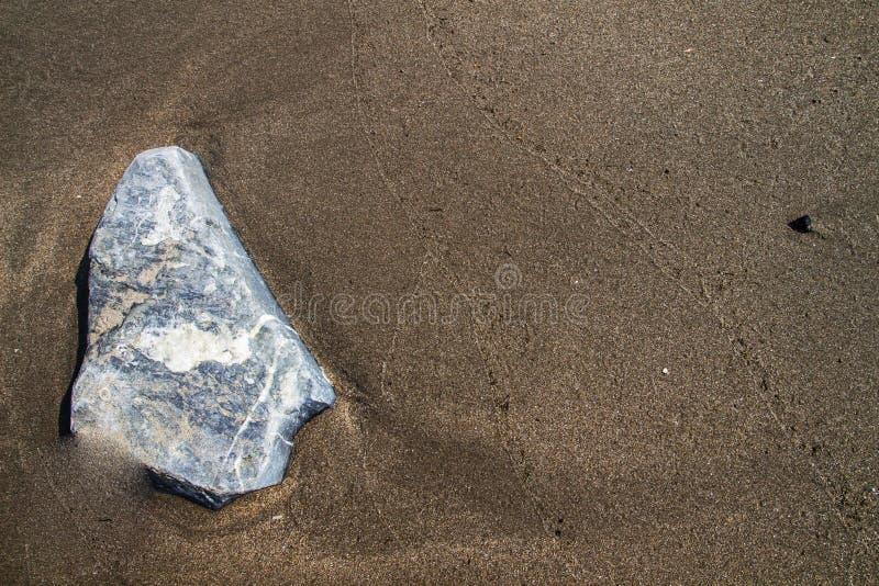 Sabbia di Brown sulla spiaggia con struttura della roccia. fotografia stock