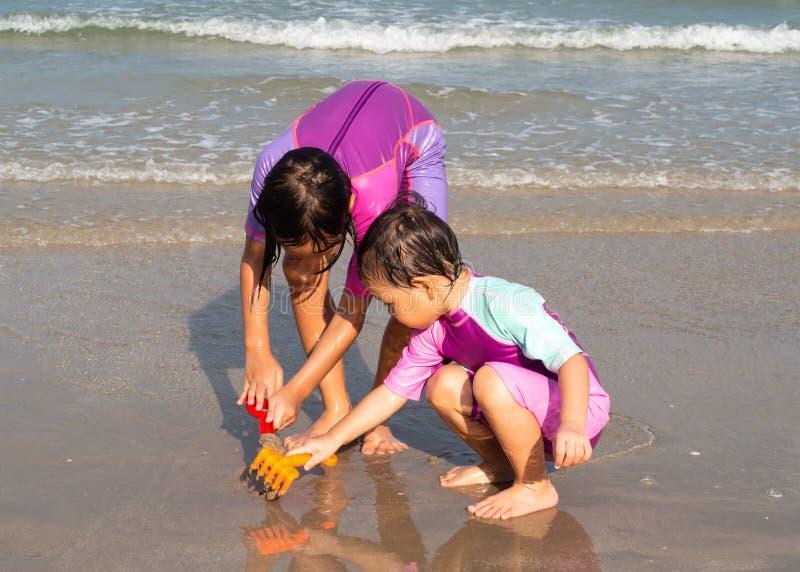 Sabbia di plastica di vangata del giocattolo di uso asiatico della ragazza due in mare Fratello germano in vestito di nuoto Attiv fotografia stock libera da diritti