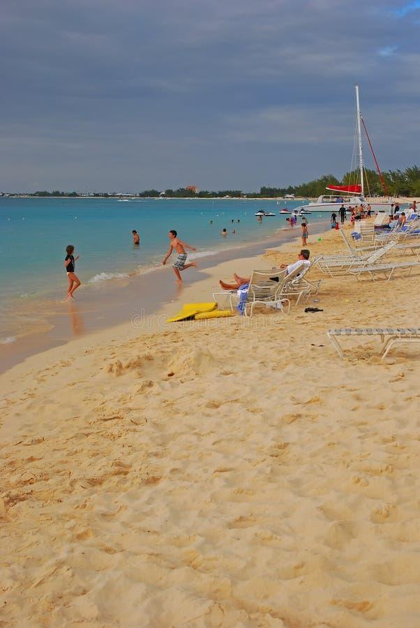 Sabbia e folla bianche fini ad una spiaggia da sette miglia, isola di caimano immagini stock