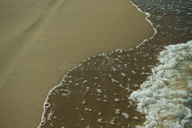Sabbia e primo piano della schiuma del mare immagini stock
