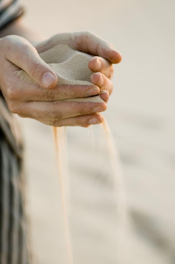 Sabbia fine che cola tramite le mani - deserto di Sahara, verticale fotografia stock