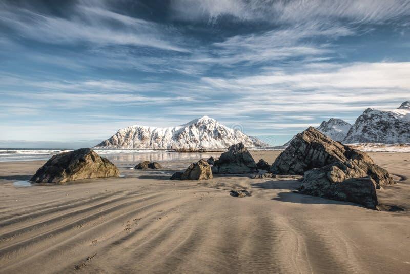Sabbia naturale del solco con la montagna ed il cielo blu della neve alla spiaggia di Skagsanden fotografia stock libera da diritti