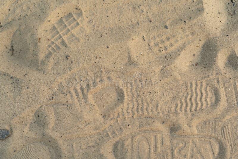 Sabbia sulla spiaggia con le orme e le scarpe Molte orme con le scarpe e senza scarpe immagini stock