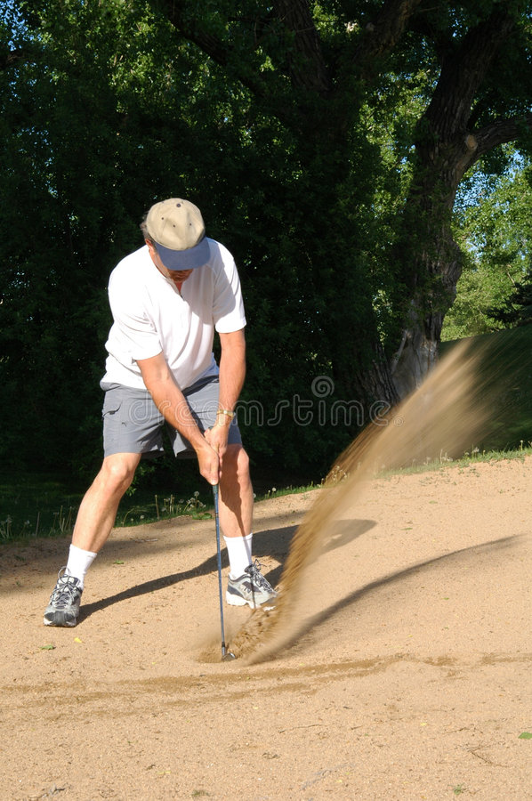 Sabd Trap. Sand flys as a man hits a ball in a sand trap royalty free stock photography