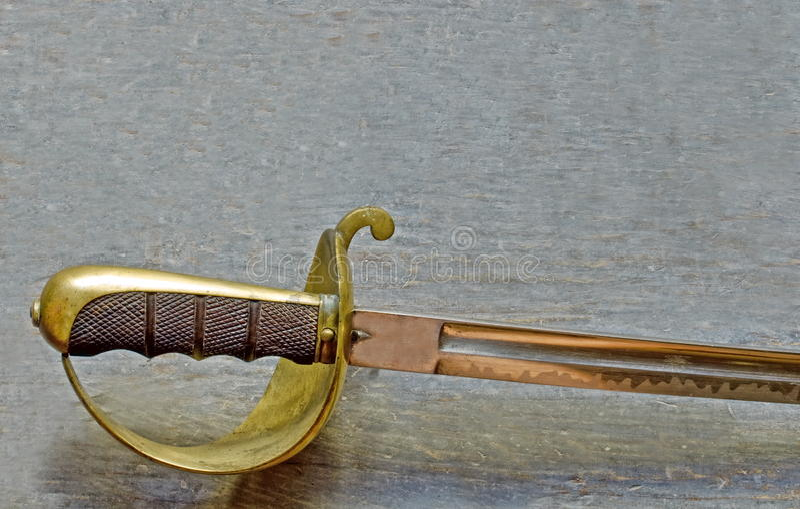 Saber handle. Detail shot of old saber on wooden surface stock photos