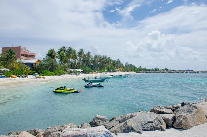 Sable blanc et pierres d'océan bleu d'île Maldive de paysage à terre photographie stock