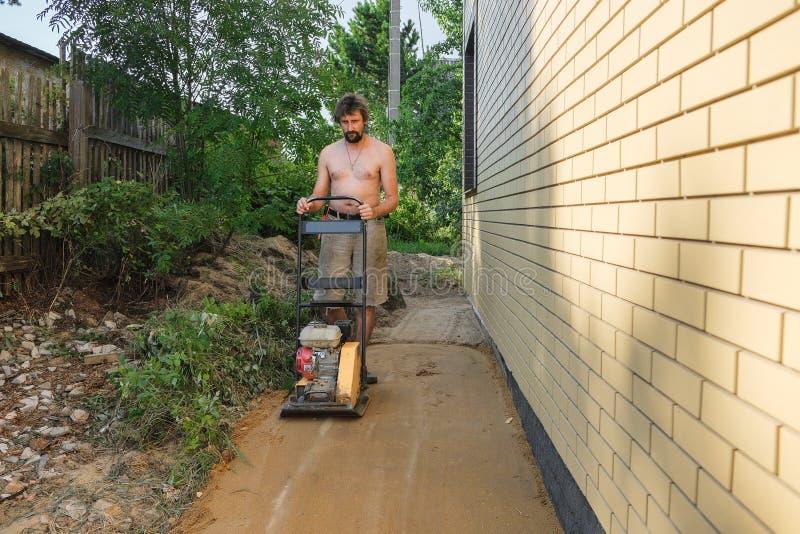 Sable de enfoncement de constructeur autour de la maison au chantier de construction photos libres de droits