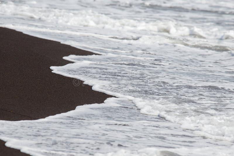 Sable et vagues volcaniques noirs sur la plage à Legazpi, Philippines images stock