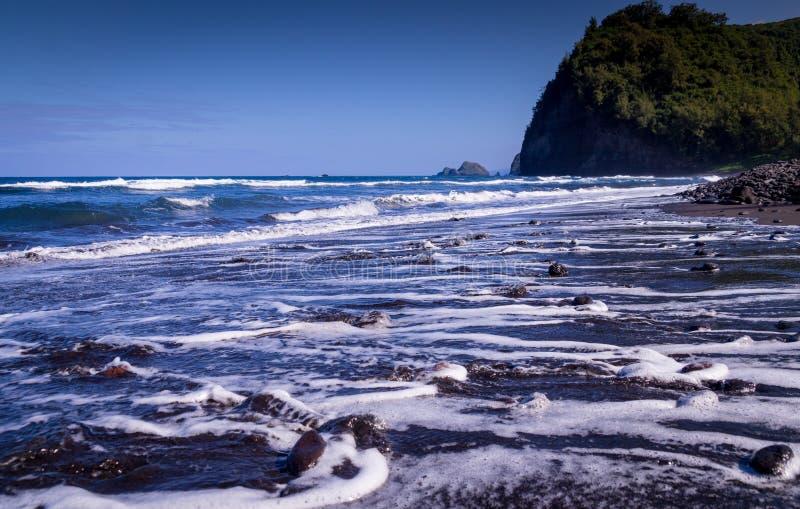 Sable noir Pebble Beach en vallée de Pololu, Hawaï image libre de droits