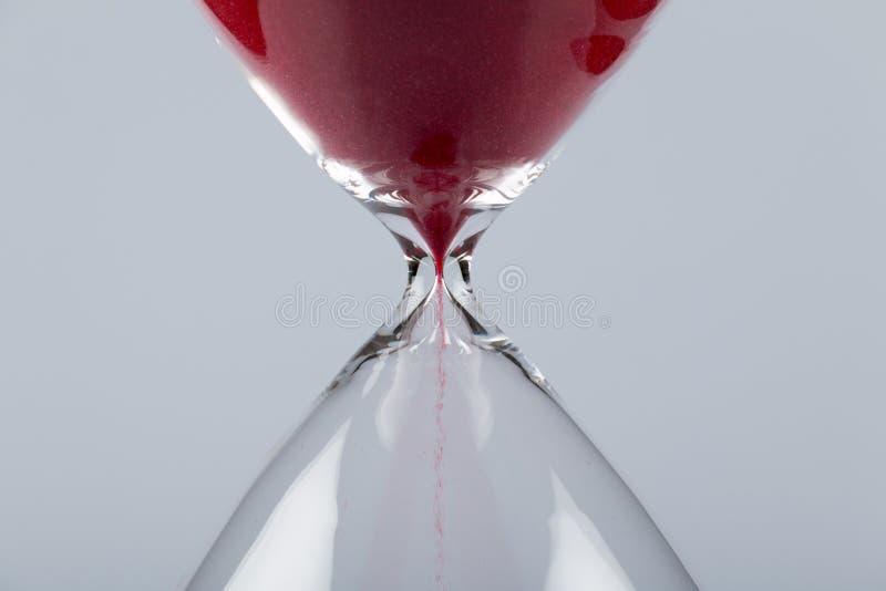 Sable rouge dans un sablier, horizontal image libre de droits