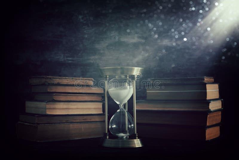 Sablier comme temps passant le concept et les vieux livres devant le fond noir de mur Photo conceptuelle sur l'histoire, imaginat illustration de vecteur