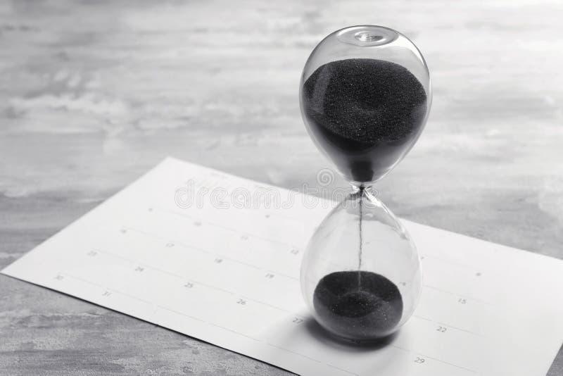 Sablier en cristal avec le sable noir et calendrier sur la table grise image stock