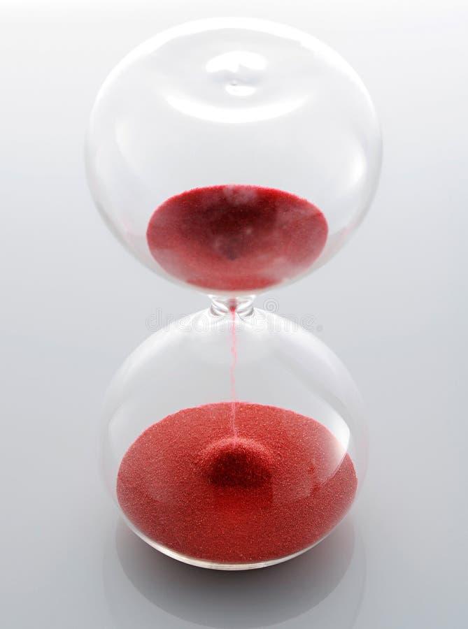 Sablier en verre clair avec le sable rouge image stock