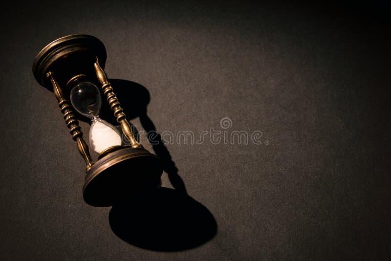 Sablier ou sandglass de cru sur un fond foncé avec l'ombre blanc au moment de l'exécution d'isolement par concept de fond image stock