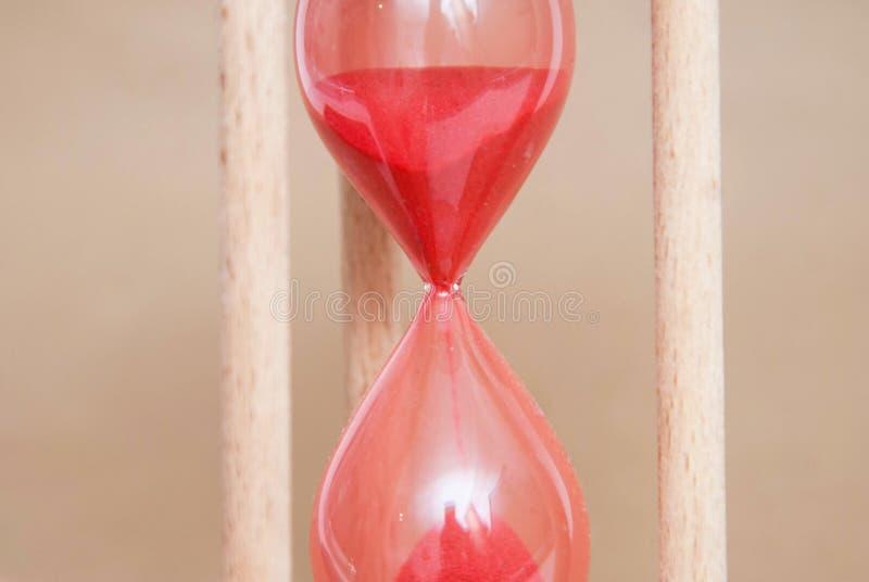 Sablier rouge en bois comme temps passant le concept et le fonctionnement hors du temps Sandglass Fond en ivoire neutre photo libre de droits