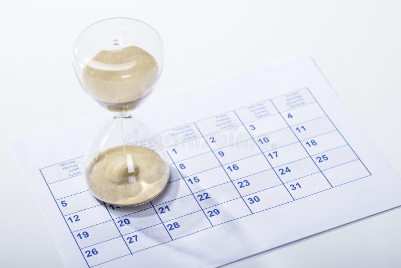 Sablier sur la feuille de calendrier images stock