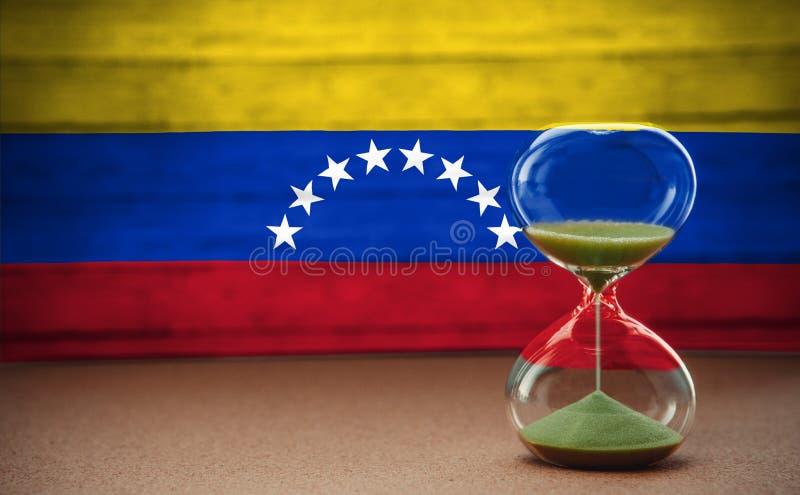 Sablier sur le fond du drapeau du Venezuela, le concept du temps et les pays, l'espace pour le texte photo stock