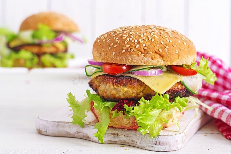 Sabroso asó a la parrilla la hamburguesa hecha en casa con el pollo de la hamburguesa, tomate, queso imagen de archivo libre de regalías