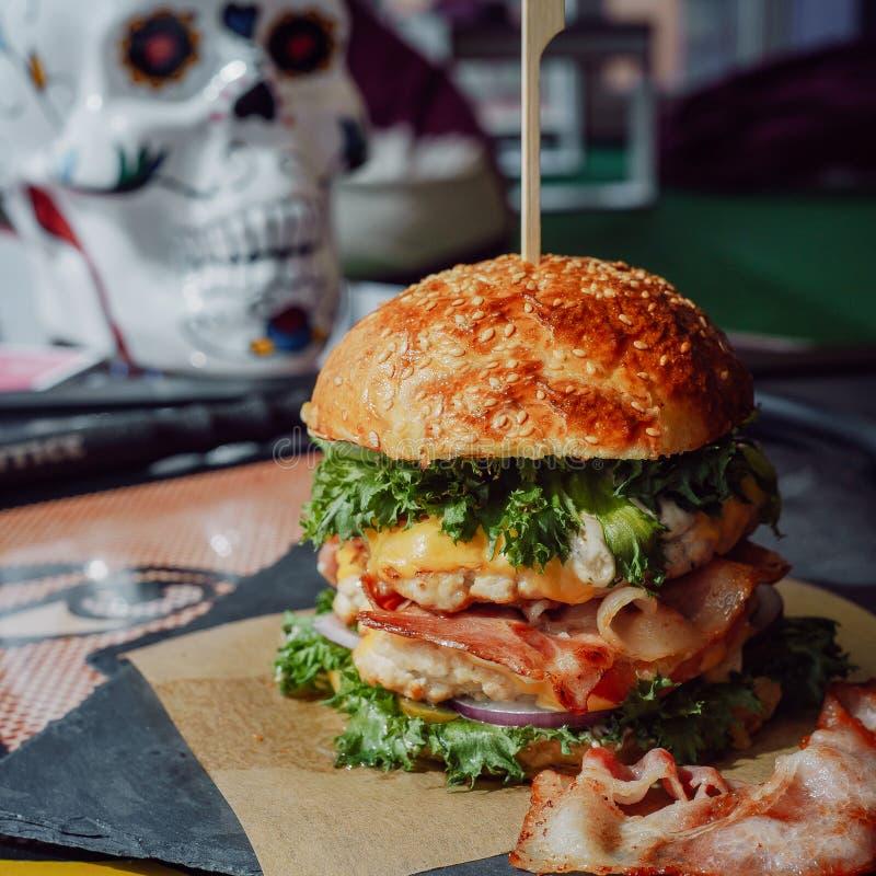 Sabrosos frescos chiken y la hamburguesa del tocino con rojo, imagen de archivo libre de regalías