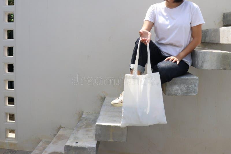 Sac à dents en tissu blanc vierge pour économiser l'environnement en mode rue avec t-shirt blanc images stock