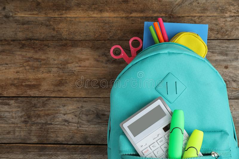 Sac à dos élégant avec l'école différente stationnaire sur la table en bois, vue supérieure photos stock