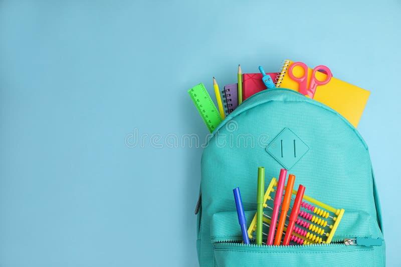 Sac à dos élégant avec l'école différente stationnaire sur le fond bleu-clair L'espace pour le texte photographie stock libre de droits