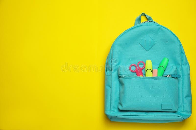 Sac à dos élégant avec l'école différente stationnaire sur le fond jaune, vue supérieure photos stock