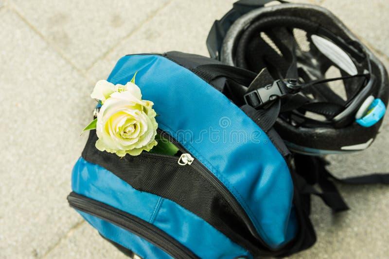 Sac à dos bleu avec le casque de bicyclette et la rose ridés de blanc, aventure, voyageant, concept romantique photographie stock libre de droits
