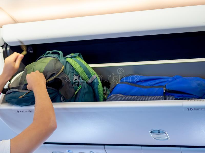 Sac à dos de putting green de main sur le casier d'avion photographie stock libre de droits