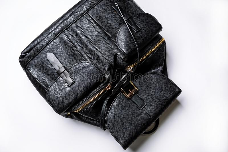 Sac à dos en cuir noir avec les poches d'or de tirette sur un fond blanc photo stock