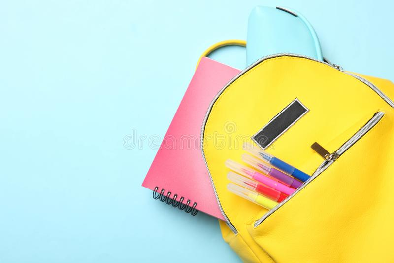 Sac à dos jaune avec différentes fournitures scolaires photographie stock