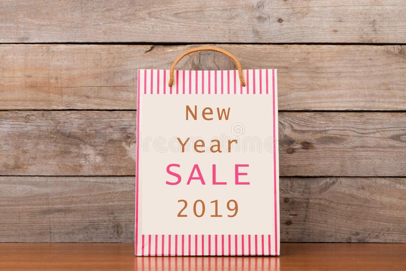 """Sac à provisions de carton avec de """"la vente 2019 nouvelle année """"des textes image stock"""