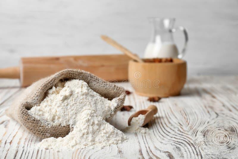 Sac avec de la farine sur la table images stock