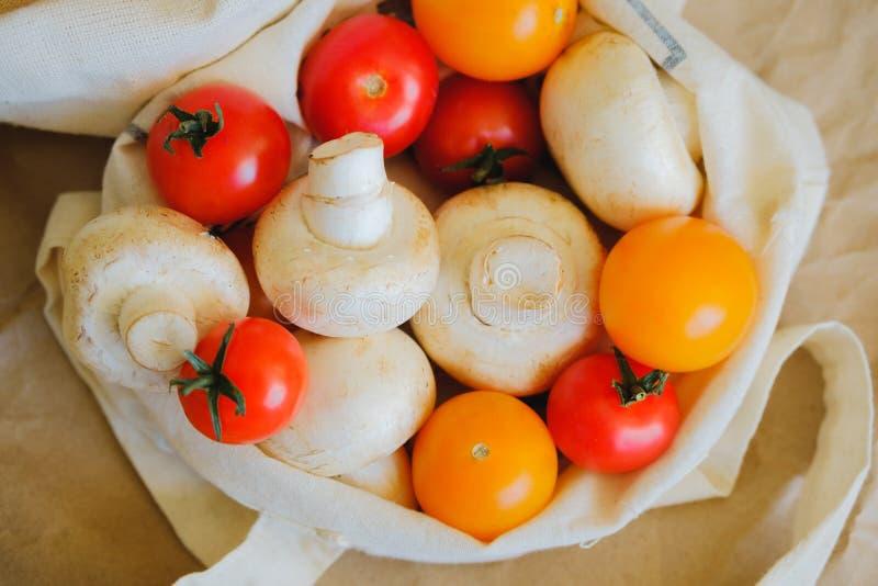 Sac blanc d'eco dans lequel les champignons et les tomates-cerises se situent photos stock