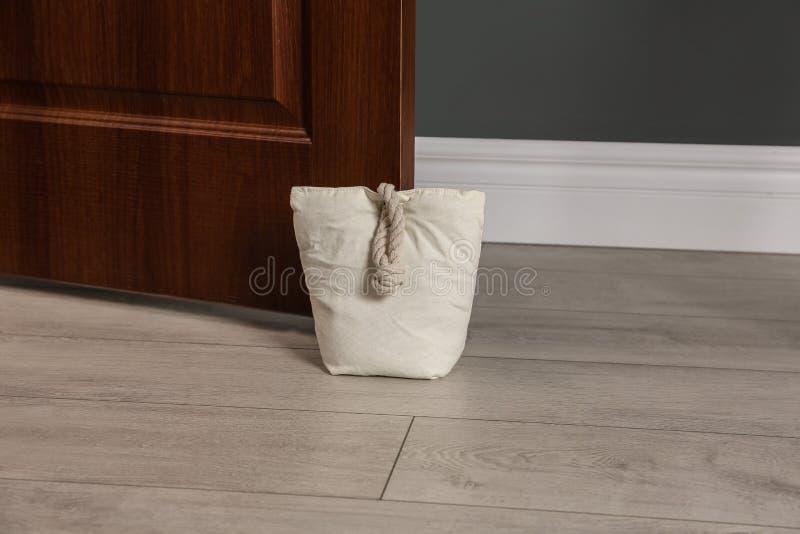Sac bourré tenant la porte en bois photographie stock