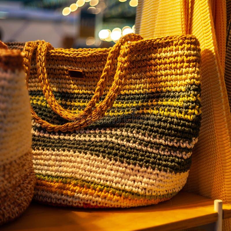 1 sac coloré par crochet au foyer se tenant du plat en bois de jeu d'intérieur au stand d'exposition, une lumière jaune chaude d' photographie stock