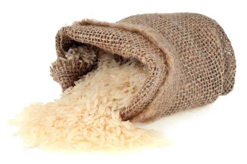 Sac cru de riz renversé sur le fond blanc photo libre de droits