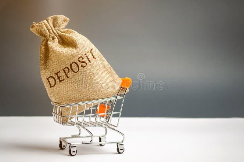 Sac d'argent avec le dépôt de mot dans un chariot à supermarché La somme d'argent a transféré par une personne à un établissement images libres de droits