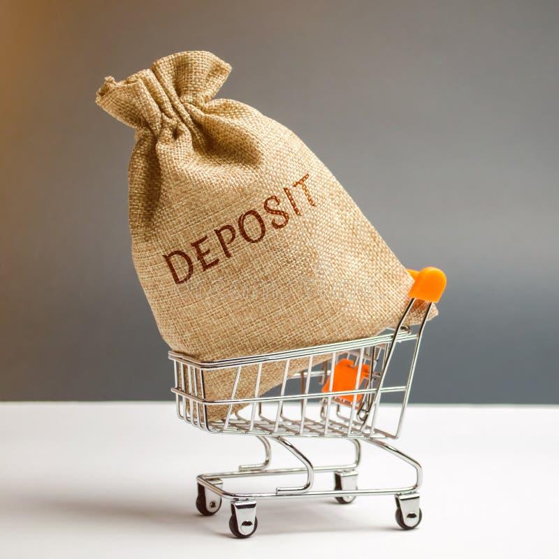 Sac d'argent avec le dépôt de mot dans un chariot à supermarché La somme d'argent a transféré par une personne à un établissement image stock